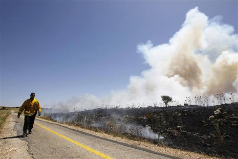 An Israeli firefighter walks past smoke from brush fires set off by stray mortar bombs fired during fighting between forces loyal to the Syr