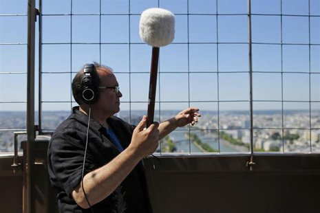 U.S. composer Joseph Bertolozzi makes sounds by striking the surface of the Eiffel Tower for a musical project called 'Tower music' in Paris