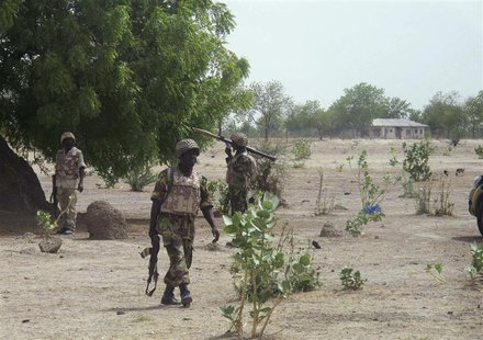 Soldiers walk through Hausari village during a military patrol near Maiduguri June 5, 2013. REUTERS/Joe Brock
