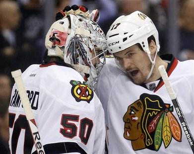 Chicago Blackhawks goalie Corey Crawford (50) gets a pat on the head from defenseman Sheldon Brookbank after their team defeated the Los Ang