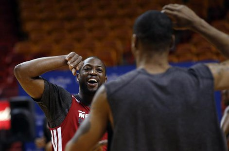 Miami Heat players Dwyane Wade (L) and Rashard Lewis react during a team practice ahead of Game 2 of the NBA Finals basketball playoff again
