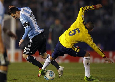 Lionel Messi (L) of Argentina tries to dribbles the ball under pressure from Aldo Ramirez of Colombia during their 2014 World Cup qualifying
