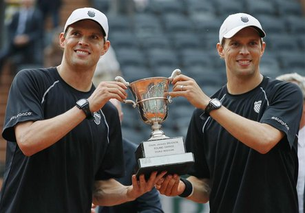Bob Bryan and Mike Bryan of the U.S. pose with their trophy after defeating Michael Llodra and Nicolas Mahut of France in their men's double