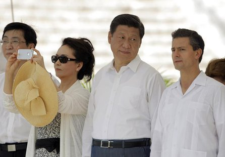 China's first lady Peng Liyuan (2nd L) takes a photograph as China's President Xi Jinping (2nd R) talks with his Mexican counterpart Enrique