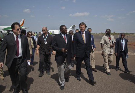 Bert Koenders (center R), United Nations special envoy for Mali, is greeted by Mali's foreign affairs General Secretary Sekouba Cisse (cente