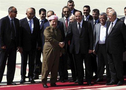 Iraqi Prime Minister Nuri al-Maliki (centre R) shakes hands with Iraqi Kurdish President Masoud Barzani (centre L) in Arbil, about 350 km (2