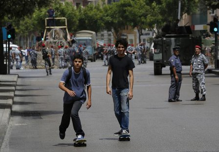 Two youths on skateboards pass by a police officer and a soldier securing a street they have closed off, where anti-Hezbollah activists had