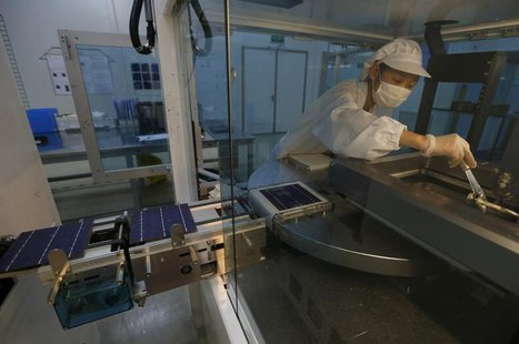 An employee works on a production line of solar panel at a factory of a photovoltaic company in Jiaxing, Zhejiang province June 5, 2013. REU