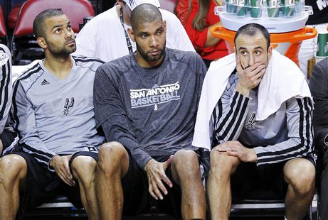 San Antonio Spurs' Tony Parker (L), Tim Duncan (C), and Manu Ginobili sit on the bench during their loss to the Miami Heat in Game 2 of thei