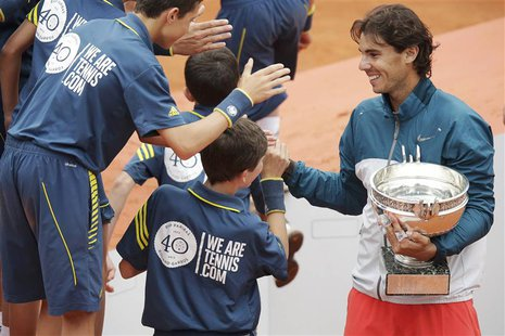 Rafael Nadal of Spain holds his trophy as he shakes hands with ball boys after defeating compatriot David Ferrer in their men's singles fina