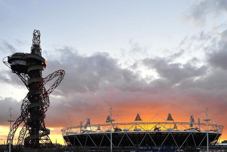 The sun sets behind the Olympic Stadium and Orbit tower at the Olympic Park in Stratford in east London March 7, 2012. REUTERS/Toby Melville