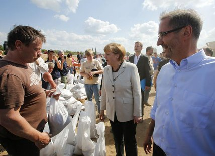 German Chancellor Angela Merkel and Brandenburg State Premier Matthias Platzeck (R) meet volunteers reinforcing a dyke at the bank of the ri