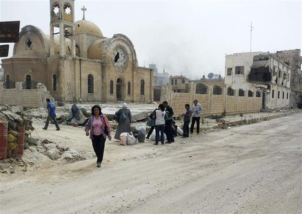 Residents walk near a damaged church as they are seen in Qusair to inspect their houses and collect their belongings June 8, 2013. REUTERS/R