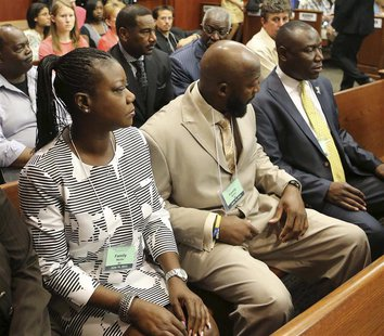 Tracy Martin and Sybrina Fulton (L), the parents of slain teen Trayvon Martin, with their attorney Benjamin Crump (R), watch the proceedings