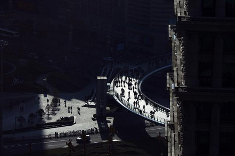 People walk at the financial district of Pudong in Shanghai January 17, 2012. REUTERS/Carlos Barria