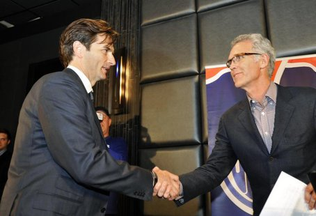 Dallas Eakins shakes hands with Edmonton Oilers' General Manager Craig MacTavish (R) during a news conference announcing Eakins' hiring as h