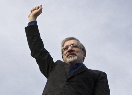 Iran's presidential election candidate Mirhossein Mousavi waves to supporters during an election campaign at a stadium in southern Tehran Ju