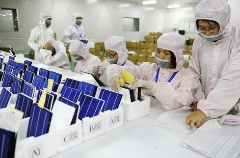 Employees inspect and sort solar panels into different quality categories at an LDK Solar company workshop in Hefei, Anhui province in this