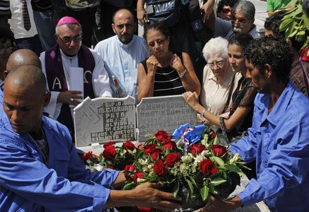 Ofelia Acevedo, wife of Oswaldo Paya, (C), one of Cuba's best-known dissidents, mourns as cemetery workers place a crown of flowers on the t