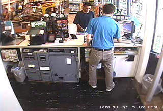 This surveillance photo shows a man (in black, facing the camera) suspected of stealing a minivan with a child inside from a parking lot in Fond du Lac on June 10, 2013.