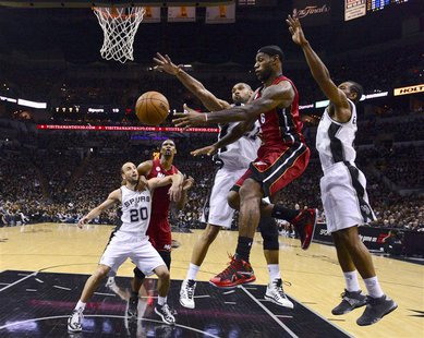 Miami Heat LeBron James (2nd R) has to pass off as San Antonio Spurs Tim Duncan (C) and Kawhi Leonard (R) defend during Game 3 of their NBA