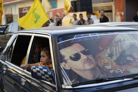 An image of Syria's President Bashar al-Assad is seen on a car's windscreen as Hezbollah supporters celebrate, after the Syrian army took co