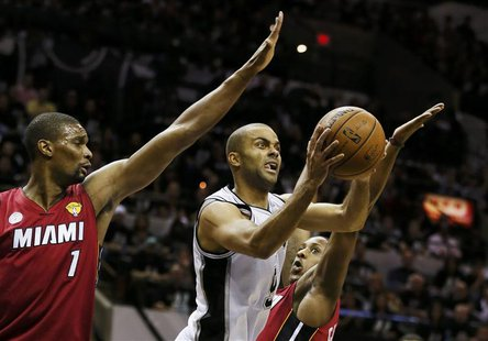 San Antonio Spurs' Tony Parker drives to the net between Miami Heat's Chris Bosh (L) and Mario Chalmers during the first quarter in Game 3 o