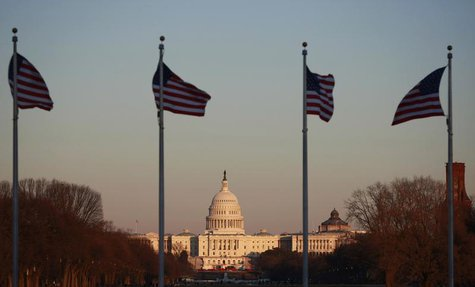 Flags at the Washington Monument flutter in the breeze as the sun casts its last rays on the U.S. Capitol Building in Washington February 5,