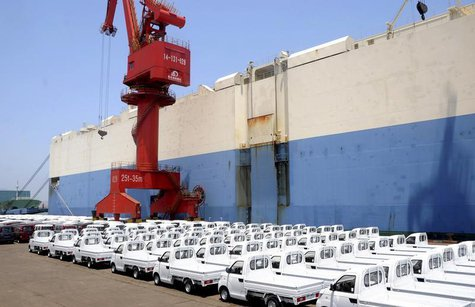 New trucks manufactured by Chinese automaker Chery are parked before being loading for export, next to a ship at a port in Lianyungang, Jian