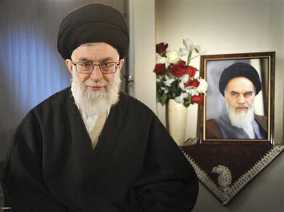 Iran's Supreme Leader Ayatollah Ali Khamenei sits next to a portrait of late leader Ayatollah Ruhollah Khomeini while taking part in a telev