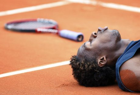 France's Gael Monfils lies on the court during his semi-final match against Switzerland's Roger Federer at the French Open tennis tournament