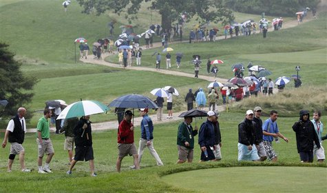 Spectators walk in the rain during a practice round for the 2013 U.S. Open golf championship at the Merion Golf Club in Ardmore, Pennsylvani