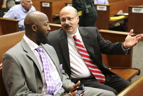 Assistant State Attorney Bernie de la Rionda (R) talks to Tracy Martin, the father of Trayvon Martin, at the George Zimmerman trial in Semin