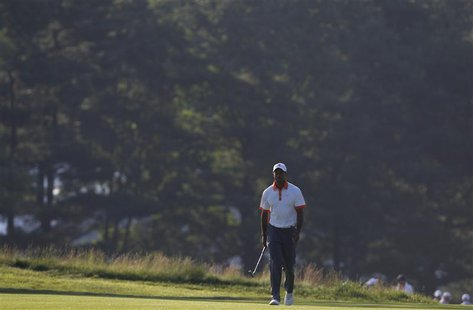 Tiger Woods of the U.S. walks on the 14th fairway during a practice round for the 2013 U.S. Open golf championship at the Merion Golf Club i