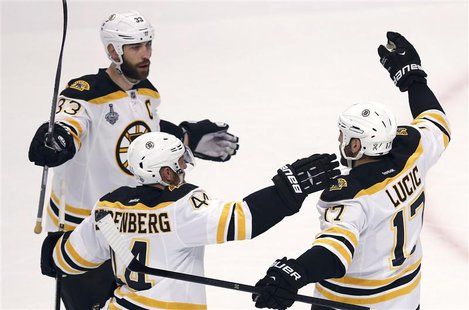 Boston Bruins' Milan Lucic (R) is congratulated by teammates Zdeno Chara (L) and Dennis Seidenberg after scoring on the Chicago Blackhawks d