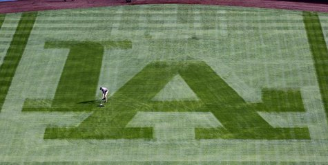 A Los Angeles Dodgers grounds crewman sweeps away the dew from the centerfield grass to prepare the field to play against the San Francisco