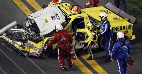Jason Leffler is pulled from his number 18 Toyota after a crash in the NASCAR Camping World Series NextEra Energy Resources 250 truck race a