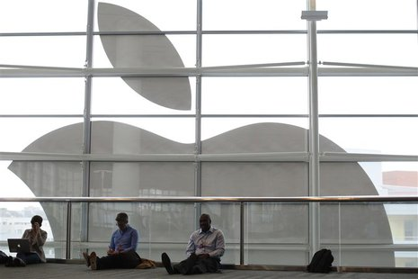 Attendees sit in front of an Apple logo at the Apple Worldwide Developers Conference (WWDC) 2013 in San Francisco, California June 10, 2013.