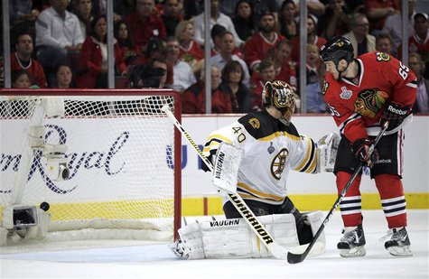 Chicago Blackhawks' Andrew Shaw (65) scores the game-winning goal past Boston Bruins goalie Tuukka Rask during triple overtime in Game 1 of