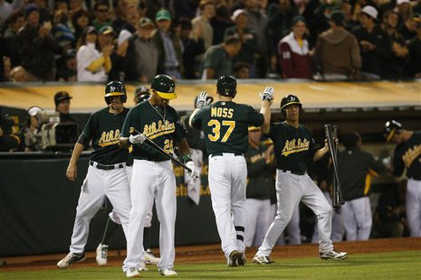 Oakland Athletics Brandon Moss celebrates with teammates after hitting a solo home run during the eighth inning of their MLB American League