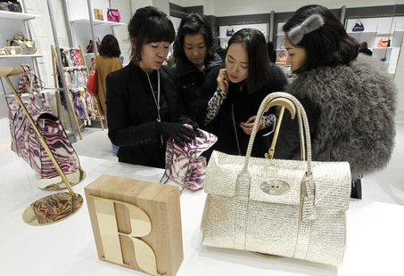 A saleswoman for British fashion brand Mulberry talks about one of the brand's bags to customers at a shop at Lotte Premium Outlets in Paju,