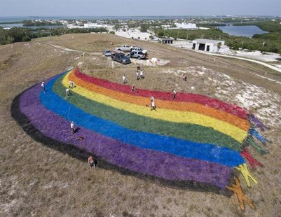 "Landscape ""artists"" put finishing touches on a giant rainbow flag on the top of a dormant landfill, nicknamed Mount Trashmore, in Key West,"