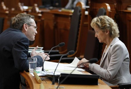 Swiss Finance Minister Eveline Widmer-Schlumpf (R) talks to Councillor of State Primin Bischof during a debate on the tax agreement between