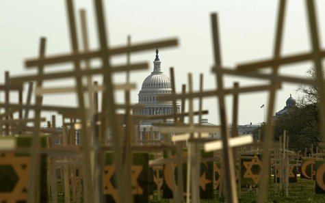 With the U.S. Capitol in the background, crosses symbolizing grave markers are placed upon the National Mall in Washington April 11, 2013. R