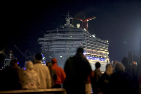 The Carnival Triumph cruise ship is towed towards the dock as spectators watch at the port of Mobile, Alabama, February 14, 2013. REUTERS/ L