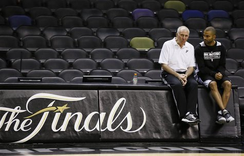 San Antonio Spurs coach Gregg Popovich (L) sits with player Tony Parker, who injured his hamstring during Game 3, during practice for their