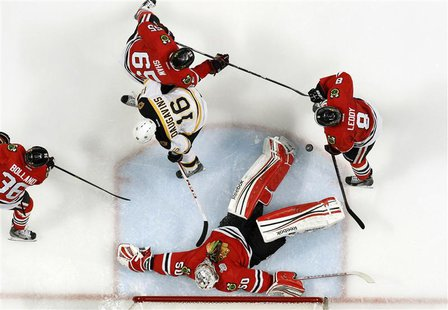 Chicago Blackhawks goalie Corey Crawford (50) makes a save on Boston Bruins left wing Kaspars Daugavins (16) during Game 1 of their NHL Stan