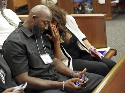 Attorney Natalie Jackson talks to Tracy Martin, father of Trayvon Martin, in Seminole circuit court during the fourth day of jury selection