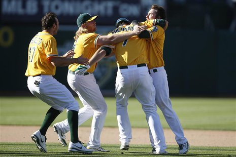 Oakland Athletics' Nate Freiman (2nd R) is congratulated by teammates after hitting the game-winning single during the 18th inning of their