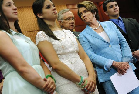 U.S. Senate Majority Leader Harry Reid (D-NV) (3rd L) and House Minority Leader Nancy Pelosi (D-CA) (2nd R) stand with Jillian Soto (L), Car